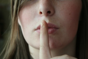 Finger over mouth denoting secrecy